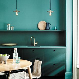 Неиссякаемый источник вдохновения для домашнего уюта: кухня в современном стиле с плоскими фасадами, зелеными фасадами, зеленым фартуком, зеленой столешницей, обеденным столом, одинарной раковиной и темным паркетным полом