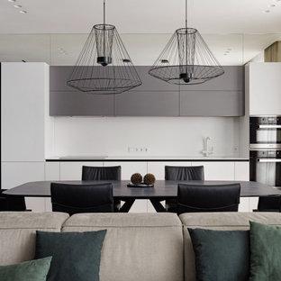 Свежая идея для дизайна: прямая кухня-гостиная в современном стиле с плоскими фасадами, белыми фасадами, белым фартуком, черной техникой и белой столешницей - отличное фото интерьера