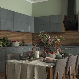 Пример оригинального дизайна: угловая кухня в современном стиле с накладной раковиной, плоскими фасадами, серыми фасадами, коричневым фартуком, бежевым полом и серой столешницей без острова