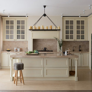 Идея дизайна: угловая кухня в стиле современная классика с обеденным столом, мраморной столешницей, фартуком из травертина, полом из травертина, островом, фасадами с утопленной филенкой, белыми фасадами, бежевым фартуком, бежевым полом, бежевой столешницей, цветной техникой и врезной раковиной