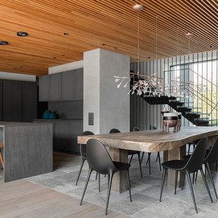Удачное сочетание для дизайна помещения: угловая кухня-гостиная в современном стиле с плоскими фасадами, черными фасадами, черным фартуком, островом, серым полом и черной столешницей - самое интересное для вас