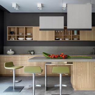 Пример оригинального дизайна: кухня в современном стиле с плоскими фасадами, светлыми деревянными фасадами, серым фартуком, островом, серым полом и серой столешницей