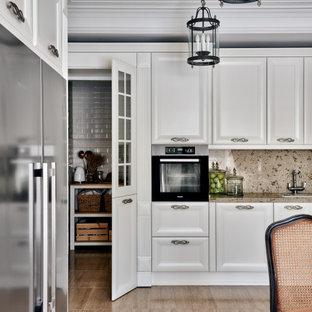 На фото: кухня в стиле неоклассика (современная классика) с кладовкой, фасадами с утопленной филенкой, белыми фасадами, бежевым фартуком, черной техникой, бежевым полом, бежевой столешницей и многоуровневым потолком в частном доме
