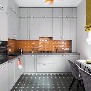 Geschlossene Moderne Küche ohne Insel in L-Form mit Schrankfronten mit vertiefter Füllung, grauen Schränken, Küchenrückwand in Orange, Rückwand aus Metrofliesen, schwarzen Elektrogeräten, grauem Boden und grauer Arbeitsplatte