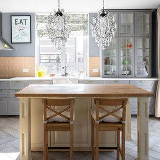 Идея дизайна: кухня-гостиная в классическом стиле с раковиной в стиле кантри, фасадами с выступающей филенкой, синими фасадами, оранжевым фартуком, фартуком из плитки кабанчик, техникой из нержавеющей стали, островом, серым полом и белой столешницей
