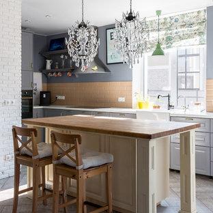 Источник вдохновения для домашнего уюта: кухня в классическом стиле с раковиной в стиле кантри, фасадами с выступающей филенкой, серыми фасадами, бежевым фартуком, фартуком из плитки кабанчик, островом, белой столешницей и бежевым полом