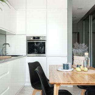 Пример оригинального дизайна: угловая кухня-гостиная в скандинавском стиле с накладной раковиной, плоскими фасадами, белыми фасадами, техникой из нержавеющей стали, светлым паркетным полом, серым полом, серой столешницей и фартуком из зеркальной плитки без острова