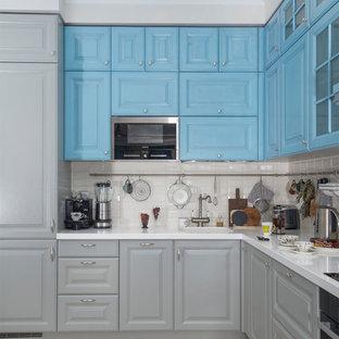 На фото: угловая кухня в стиле современная классика с фасадами с выступающей филенкой, синими фасадами, белым фартуком, фартуком из плитки кабанчик, черной техникой, бежевым полом и обеденным столом