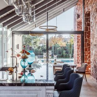 На фото: большая прямая кухня в современном стиле с обеденным столом, стеклянными фасадами, белыми фасадами, черным фартуком, техникой из нержавеющей стали, коричневым полом и островом с