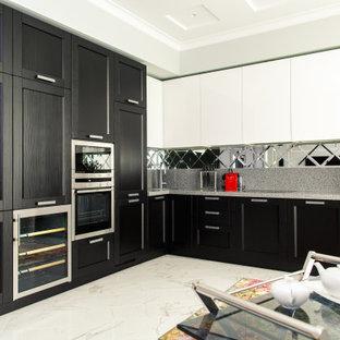 Пример оригинального дизайна: угловая кухня в современном стиле с фасадами с утопленной филенкой, черными фасадами, техникой из нержавеющей стали, белым полом и серой столешницей без острова