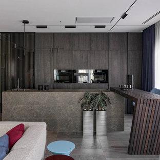 На фото: кухни-гостиные в современном стиле с одинарной раковиной, плоскими фасадами, темными деревянными фасадами, черной техникой, двумя и более островами, коричневым полом и коричневой столешницей