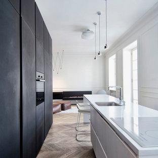 Выдающиеся фото от архитекторов и дизайнеров интерьера: линейная кухня среднего размера в скандинавском стиле с обеденным столом, врезной раковиной, плоскими фасадами, столешницей из акрилового камня, черной техникой, паркетным полом среднего тона и островом
