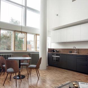 モスクワの小さいモダンスタイルのおしゃれなキッチン (シングルシンク、フラットパネル扉のキャビネット、黒いキャビネット、木材カウンター、茶色いキッチンパネル、木材のキッチンパネル、黒い調理設備、無垢フローリング、茶色い床、茶色いキッチンカウンター) の写真