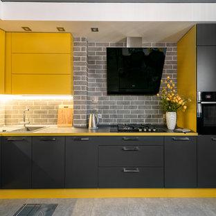 Immagine di una cucina contemporanea di medie dimensioni con lavello sottopiano, ante lisce, ante gialle, top in superficie solida, paraspruzzi nero, paraspruzzi con piastrelle in ceramica, elettrodomestici neri, pavimento in gres porcellanato, isola, pavimento grigio e top nero