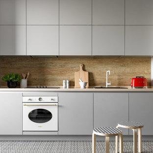 Стильный дизайн: кухня в современном стиле с плоскими фасадами, серыми фасадами, бежевым фартуком, белой техникой, бежевой столешницей и разноцветным полом - последний тренд