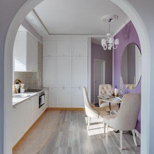 Создайте стильный интерьер: кухня в стиле современная классика с обеденным столом, фасадами с утопленной филенкой, белыми фасадами, бежевым фартуком, светлым паркетным полом и серой столешницей - последний тренд