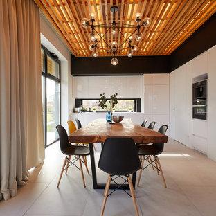 Пример оригинального дизайна интерьера: угловая кухня в современном стиле с обеденным столом, плоскими фасадами, белыми фасадами, фартуком с окном, бежевым полом и белой столешницей без острова