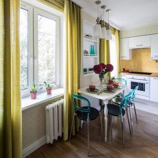 モスクワの北欧スタイルのおしゃれなキッチン (フラットパネル扉のキャビネット、白いキャビネット、黄色いキッチンパネル、白い調理設備、無垢フローリング、アイランドなし) の写真
