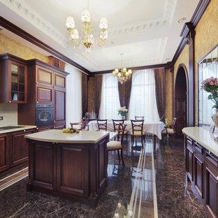 Пример оригинального дизайна: большая п-образная кухня в классическом стиле с обеденным столом, коричневыми фасадами, полом из керамогранита и островом