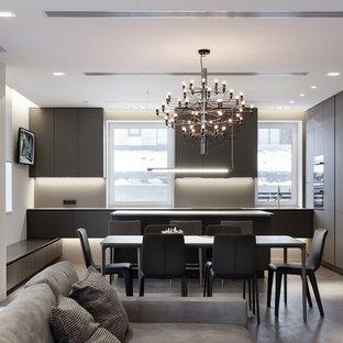 Пример оригинального дизайна интерьера: большая угловая кухня-гостиная в современном стиле с врезной раковиной, плоскими фасадами, столешницей из нержавеющей стали, фартуком из стекла, бетонным полом, островом, серыми фасадами, серым фартуком и черной техникой