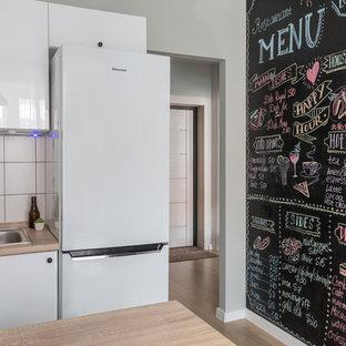Неиссякаемый источник вдохновения для домашнего уюта: маленькая п-образная кухня в скандинавском стиле с обеденным столом, накладной раковиной, плоскими фасадами, белыми фасадами, белым фартуком, полуостровом и бежевой столешницей