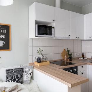 Kleine Skandinavische Wohnküche in U-Form mit Einbauwaschbecken, flächenbündigen Schrankfronten, weißen Schränken, Küchenrückwand in Weiß, Halbinsel, beiger Arbeitsplatte und Arbeitsplatte aus Holz in Sonstige