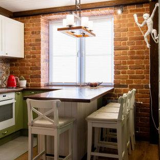 На фото: маленькая угловая кухня в стиле неоклассика (современная классика) с плоскими фасадами, зелеными фасадами, деревянной столешницей, белой техникой, паркетным полом среднего тона, полуостровом, коричневым полом, коричневой столешницей и деревянным потолком
