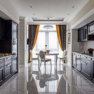 Неиссякаемый источник вдохновения для домашнего уюта: параллельная кухня среднего размера в стиле современная классика с обеденным столом, одинарной раковиной, серыми фасадами, мраморной столешницей, белым фартуком, фартуком из мрамора, полом из керамогранита, белым полом, фасадами с утопленной филенкой, черной техникой и белой столешницей без острова