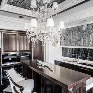Удачное сочетание для дизайна помещения: кухня в классическом стиле с врезной раковиной, черным фартуком, черной техникой, мраморным полом, островом, коричневыми фасадами и разноцветным полом - самое интересное для вас