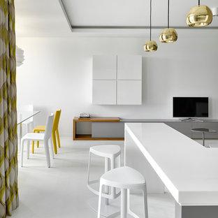 Diseño de cocina en L, actual, abierta, con fregadero bajoencimera, armarios con paneles lisos, puertas de armario blancas, encimera de cuarzo compacto, salpicadero verde, salpicadero de azulejos de porcelana, electrodomésticos de acero inoxidable, suelo de madera pintada y una isla