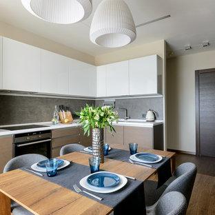 Свежая идея для дизайна: отдельная, п-образная кухня в современном стиле с плоскими фасадами, светлыми деревянными фасадами, серым фартуком, техникой из нержавеющей стали, темным паркетным полом, коричневым полом и белой столешницей без острова - отличное фото интерьера