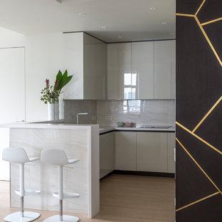 Пример оригинального дизайна: п-образная кухня-гостиная в современном стиле с плоскими фасадами, белыми фасадами, полуостровом и белой столешницей