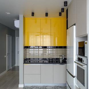 Источник вдохновения для домашнего уюта: угловая кухня в современном стиле с плоскими фасадами, желтыми фасадами, бежевым фартуком, белой техникой, светлым паркетным полом, бежевым полом, черной столешницей и фартуком из плитки кабанчик без острова