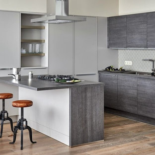 Стильный дизайн: п-образная кухня среднего размера в современном стиле с обеденным столом, одинарной раковиной, плоскими фасадами, серыми фасадами, столешницей из ламината, серым фартуком, фартуком из керамогранитной плитки, паркетным полом среднего тона, полуостровом и черной техникой - последний тренд