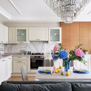 Неиссякаемый источник вдохновения для домашнего уюта: угловая кухня-гостиная в стиле современная классика с врезной раковиной, фасадами с утопленной филенкой, белыми фасадами, белым фартуком, техникой из нержавеющей стали, коричневым полом и серой столешницей без острова