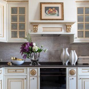 На фото: кухня в классическом стиле с фасадами с выступающей филенкой, белыми фасадами, серым фартуком, черной техникой, серым полом и черной столешницей с