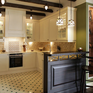 This is an example of a mid-sized traditional u-shaped open plan kitchen in Moscow with an undermount sink, recessed-panel cabinets, white cabinets, quartz benchtops, brown splashback, ceramic splashback, porcelain floors, a peninsula, multi-coloured floor, black appliances and beige benchtop.