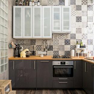 Пример оригинального дизайна: маленькая угловая кухня в современном стиле с плоскими фасадами, серыми фасадами, деревянной столешницей, темным паркетным полом, коричневым полом, обеденным столом, накладной раковиной, серым фартуком и техникой из нержавеющей стали без острова
