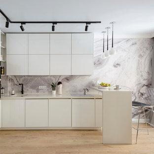 Свежая идея для дизайна: маленькая угловая кухня в современном стиле с плоскими фасадами, белыми фасадами, серым фартуком, светлым паркетным полом, полуостровом, бежевым полом и белой столешницей - отличное фото интерьера