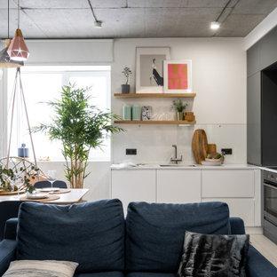 Свежая идея для дизайна: маленькая угловая кухня-гостиная в современном стиле с врезной раковиной, плоскими фасадами, серыми фасадами, техникой из нержавеющей стали, серым полом и белой столешницей без острова - отличное фото интерьера