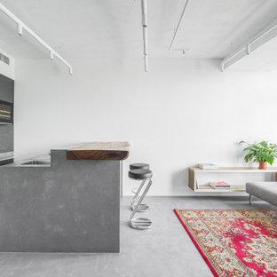 Свежая идея для дизайна: параллельная кухня среднего размера в современном стиле с врезной раковиной, плоскими фасадами, черными фасадами, серым фартуком, фартуком из керамогранитной плитки, черной техникой, полом из керамогранита, островом, серым полом и серой столешницей - отличное фото интерьера