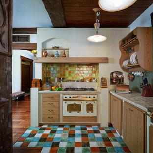 エカテリンブルクのカントリー風おしゃれなL型キッチン (中間色木目調キャビネット、マルチカラーのキッチンパネル、テラコッタタイルのキッチンパネル、テラコッタタイルの床、アイランドなし、マルチカラーの床、タイルカウンター、白い調理設備) の写真