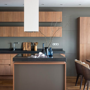 Пример оригинального дизайна: большая кухня в стиле модернизм с обеденным столом, плоскими фасадами, серым фартуком, паркетным полом среднего тона, островом, фасадами цвета дерева среднего тона, коричневым полом, врезной раковиной и техникой под мебельный фасад