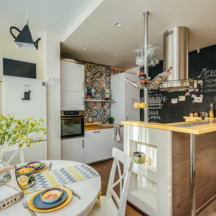 This is an example of a small eclectic galley eat-in kitchen in Moscow with a drop-in sink, flat-panel cabinets, white cabinets, multi-coloured splashback, stainless steel appliances, medium hardwood floors, with island, brown floor, yellow benchtop and ceramic splashback.