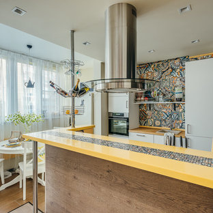 Photo of a small scandinavian galley eat-in kitchen in Moscow with flat-panel cabinets, white cabinets, brown floor, yellow benchtop, a single-bowl sink, solid surface benchtops, yellow splashback, ceramic splashback, stainless steel appliances, porcelain floors and with island.