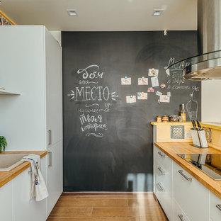 モスクワの小さい北欧スタイルのおしゃれなキッチン (ドロップインシンク、フラットパネル扉のキャビネット、白いキャビネット、木材カウンター、マルチカラーのキッチンパネル、無垢フローリング、茶色い床、茶色いキッチンカウンター、セラミックタイルのキッチンパネル、シルバーの調理設備) の写真