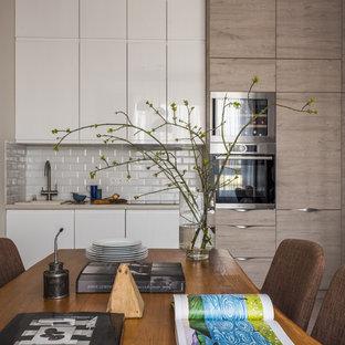 На фото: линейные кухни в современном стиле с накладной раковиной, плоскими фасадами, белым фартуком, фартуком из плитки кабанчик, бежевой столешницей, обеденным столом, белыми фасадами и техникой из нержавеющей стали без острова
