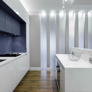 Diseño de cocina de galera, actual, de tamaño medio, abierta, con suelo de linóleo, fregadero bajoencimera, armarios con paneles lisos, puertas de armario blancas, salpicadero azul y una isla