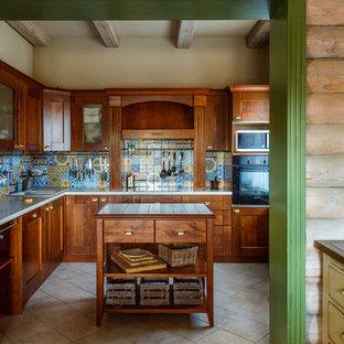 Новые идеи обустройства дома: угловая кухня в стиле кантри с накладной раковиной, фасадами в стиле шейкер, фасадами цвета дерева среднего тона, разноцветным фартуком, черной техникой, островом и бежевым полом