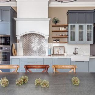 На фото: прямая кухня в стиле современная классика с серыми фасадами, белой столешницей, раковиной в стиле кантри, техникой из нержавеющей стали, обеденным столом, фасадами в стиле шейкер и коричневым фартуком без острова